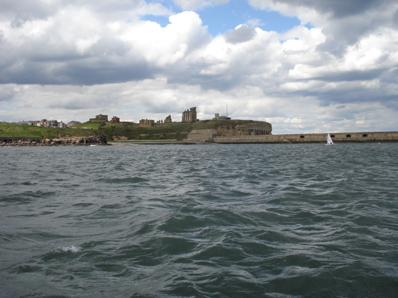 Sailing by Tynemouth Priory at the mouth of the River Tyne, Newcastle, UK